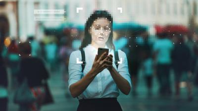 Woman on phone with people behind blurred out with face identification programing overlay